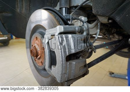 Close-up Of A Brake Caliper Mounted On A Modern Car. The Car In The Service Center Is Lifted On A Li