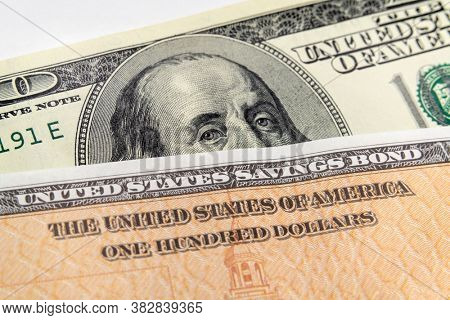 Macro view of Benjamin Franklin on the one hundred dollar bill looking over the top of a United States Savings Bond.