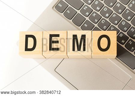 Word Demo. Wooden Cubes With Letters Isolated On A Laptop Keyboard. Business Concept Image.