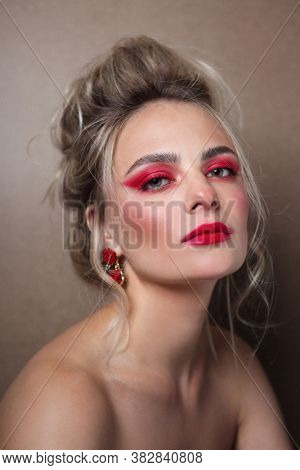 Portrait of young beautiful woman with hair bun and fancy red makeup