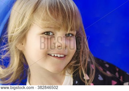 Child Portrait Of Cute Smiling Little Girl On Blue Background.