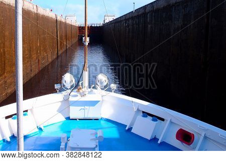 Ship Passes Through The Gateway Gate. Inside View Of A Flood Gateway. Locks Water. Device For Raisin
