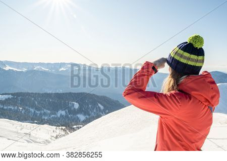 Portrait Of A Woman In A Winter Hat With A Pom-pom On A Background Of A Winter Mountain Landscape