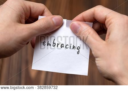 Concept Of Cancelling. Hands Closeup Tearing A Sheet Of Paper With Inscription Embracing