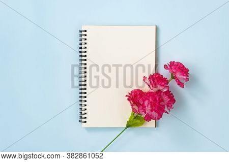 Spiral Notebook Or Spring Notebook In Unlined Type And Red Flower At Bottom Right On Blue Pastel Min