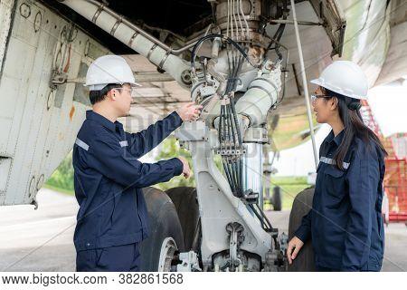 Asian Man And Woman Engineer Maintenance Airplane Team Repairs, Fixes, Modernization And Renovation