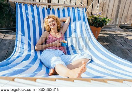 Young Beautiful Caucasian Woman Drinks Tea, Smiling Happy Resting In Comfortable Hammock At Home. Ma