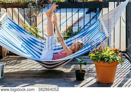 Playful Blond Curly Woman Relaxing, Stretching, Basking Sun Bath In Hammock At Cozy Terrace Outdoor.