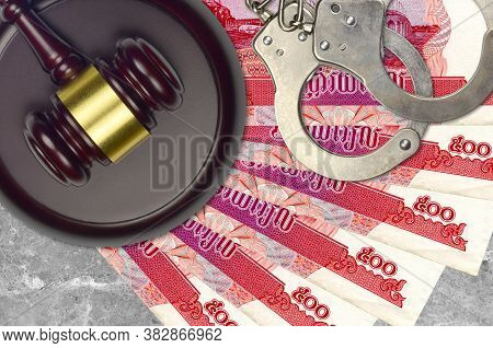 500 Cambodian Riels Bills And Judge Hammer With Police Handcuffs On Court Desk. Concept Of Judicial