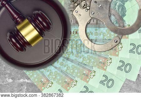 20 Ukrainian Hryvnias Bills And Judge Hammer With Police Handcuffs On Court Desk. Concept Of Judicia