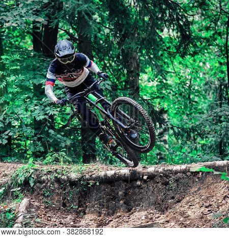 Russia, Moscow - August 29, 2020: Young Boy Jumping With His Mtb Bike At Forest. Professional Downhi