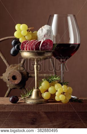 Glass Of Wine With Snacks On A Brown Background. Wine, Dry-cured Sausage, Grapes, And Rosemary On An