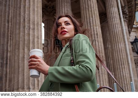 Young Brunette Woman In A Green Jacket On A Walk. Business Girl With Coffee To Take Away With Her Ha