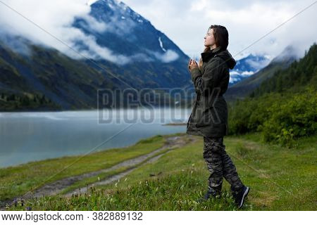 A Woman In A Warm Jacket With Long Hair Stands Against A Background Of Mountains In The Fog In Cold,