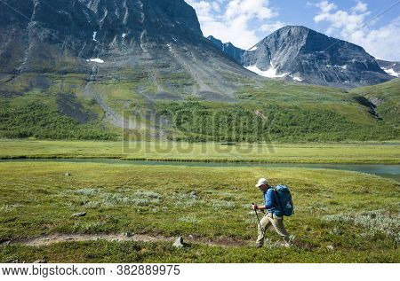 Hiking in Swedish Lapland. Man trekking alone in Vistasvagge valley in northern Sweden. Arctic mountain nature of Scandinavia in summer day