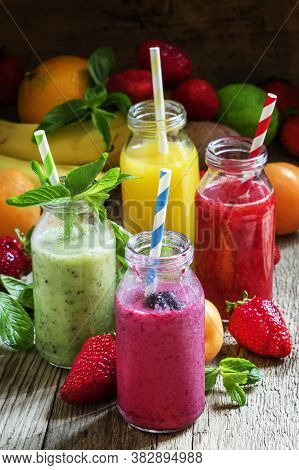 Fruit Smoothies With Colored Straws In Glass Bottles, Selective Focus