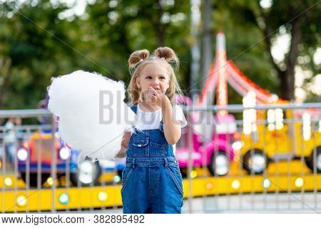 Happy Baby Girl Eating Cotton Candy At Amusement Park In Summer
