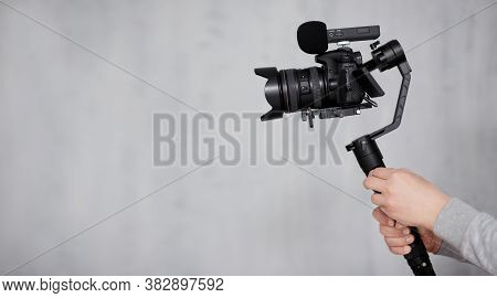 Modern Dslr Camera On 3-axis Gimbal Stabilizer With Follow Focus System In Male Videographer Hands O
