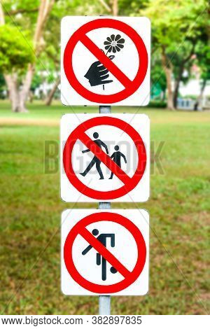 Signs Do Not Pick Flowers, Do Not Step On Grass And Not Play Football In The Park.