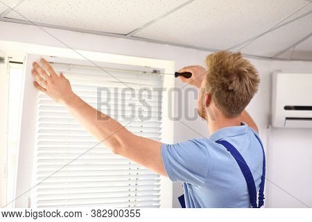 Handyman With Screwdriver Installing Window Blinds Indoors