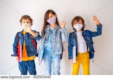 Three Children With Face Masks Ready To Go Back To School. New Normality, Social Distance, Coronavir