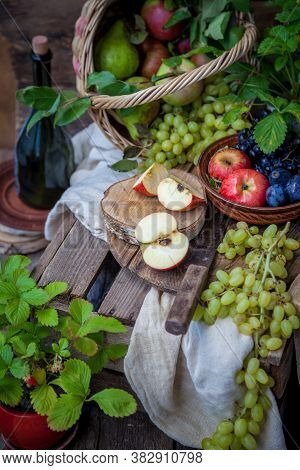 Autumn Still Life. Fruits And Berries. Apples, Grapes, Strawberries, Plums On A Wooden Table. Countr