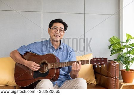 Asian Elder Man Playing Guitar At The Sofa Inside Of The House. Active Senior Lifestyle After Retire