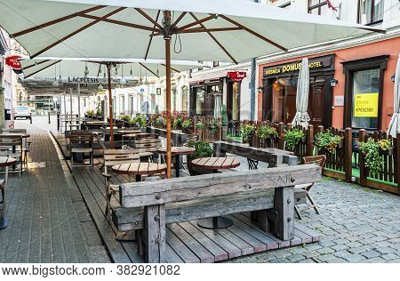 Riga, Latvia - July 28, 2019: Street Scene In The Old Town. View Of An Outdoor Restaurant In Early M
