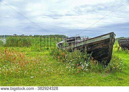 Old Wooden Boat Resting On Shore Of Jugla Lake Near Riga, Latvia