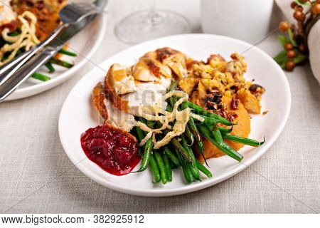 Traditional Thanksgiving Plates With Turkey, Gravy, Cranberry Sauce And Sides