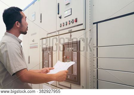Electrical Engineer Man Checking Voltage And Test At The Power Distribution Cabinet In The Control R