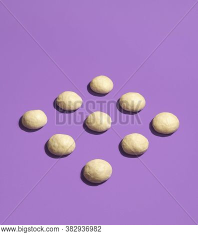 Raw Bread Buns Dough Displayed Symmetrically On A Seamless Purple Background. Unbaked Dough Balls. L