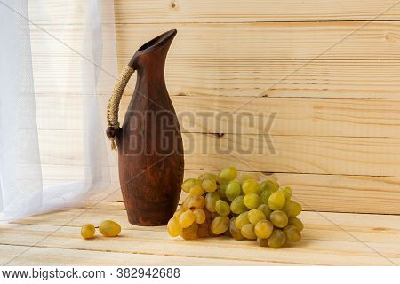 Still Life With Green Grapes And An Earthenware Jug. Grapes And A Jug On A Light Natural Wooden Back
