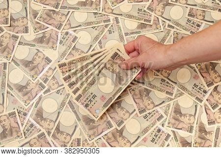 Hand Holding Five Pieces Of 10,000 Yen Notes - Background With Several Ten Thousand Yen Notes (front