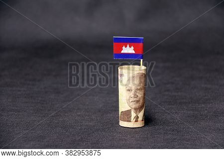 Rolled Banknote Money Five Thousand Cambodian Riel And Stick With Mini Cambodia Flag 0n Dark Grey Fl