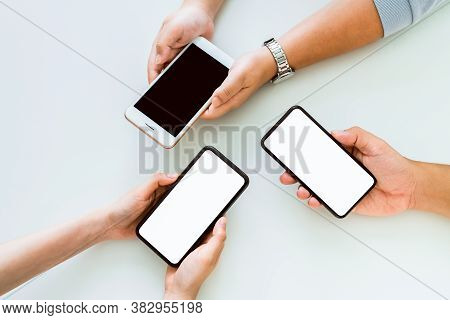 Hand Holding Smartphone Mockup Of Blank Screen On The Table. Take Your Screen To Put On Advertising.