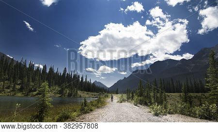 Mountain Bikers Ride The High Rockies Trail Through Peter Lougheed Provincial Park Under A Dramatic