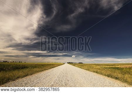 Scenic Route Down A Rural Gravel Road Along The Alberta Prairies Under A Deep Blue Sky In Rocky View