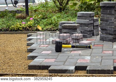 A Worker Installs Paving Slabs In The Yard. Laying Gray Concrete Paving Slabs In The Courtyard Of Th