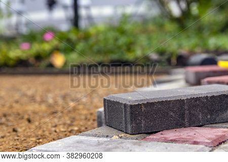 The Device Of The Sidewalk Near The House. A Bricklayer Lays Concrete Paving Stones For The Sidewalk