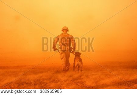 Military Soldier With A Dog Between Storm And Dust At Desert