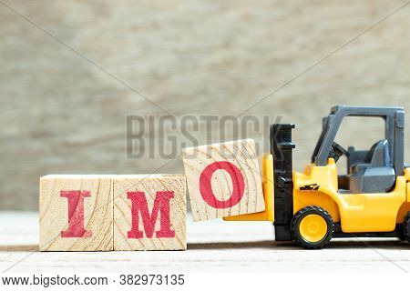 Toy Forklift Hold Letter Block O To Complete Word Imo (abbreviation Of In My Opinion) On Wood Backgr