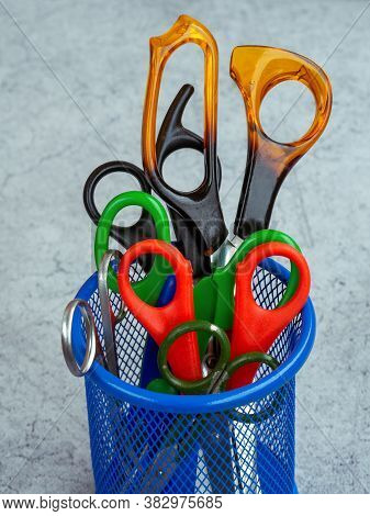 Scissors Of Different Sizes And For Different Purposes Are Neatly Inserted Into A Round Mesh Stand.