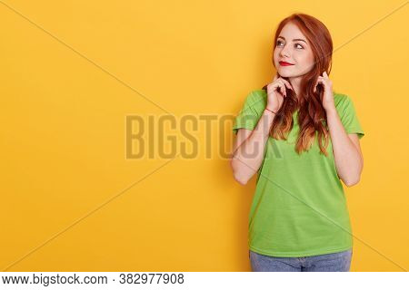 Photo Of Lovely Ginger Woman Looking Aside, Looks With Interesting Expression, Has Wavy Red Hair, We
