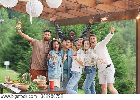 Multi-ethnic Group Of Happy Friends Holding Sparklers And Looking At Camera While Enjoying Summer Pa