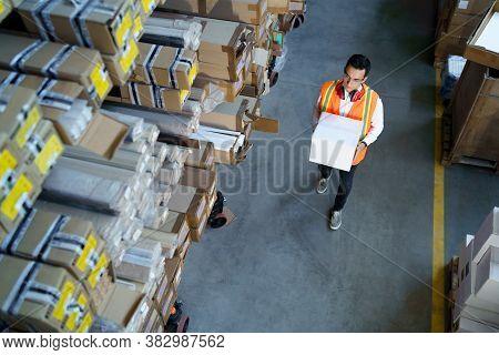 Warehouse Worker Walks With A Box. Hard Work