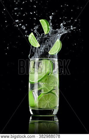A Glass Of Lime Lemonade With Ice, Splashing In Different Directions And Three Slices Of Lime Fallin