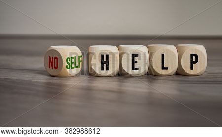Cubes And Dice With The Words No Help And Self Help On Wooden Background