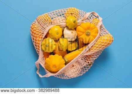 Fresh Harvest Of Zucchini And Pattypan Squash, Yellow Squash And Pattison In A Food Grid On Blue Bac