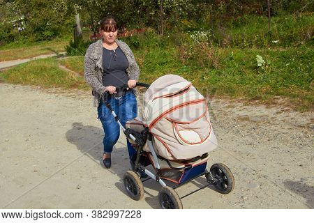 Woman On A Walk With A Stroller, In The Countryside A Woman Pushes A Stroller With A Newborn Baby